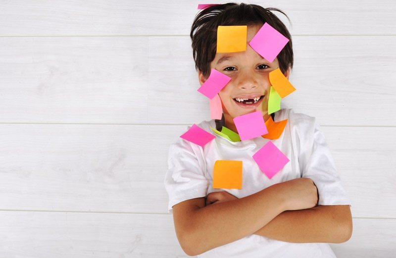smiling kid with sticky notes on face