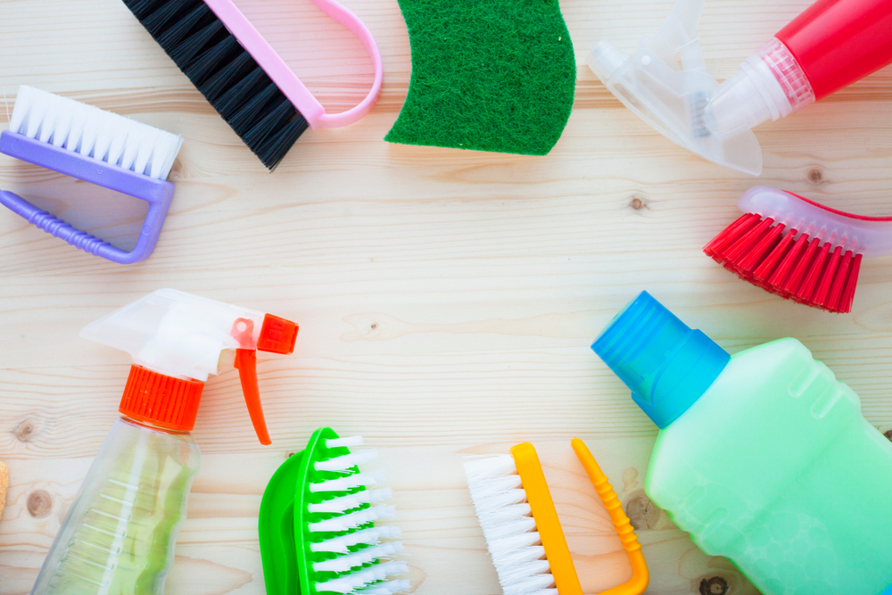 set of cleaning tools on light wooden background, top view, flat lay, close up
