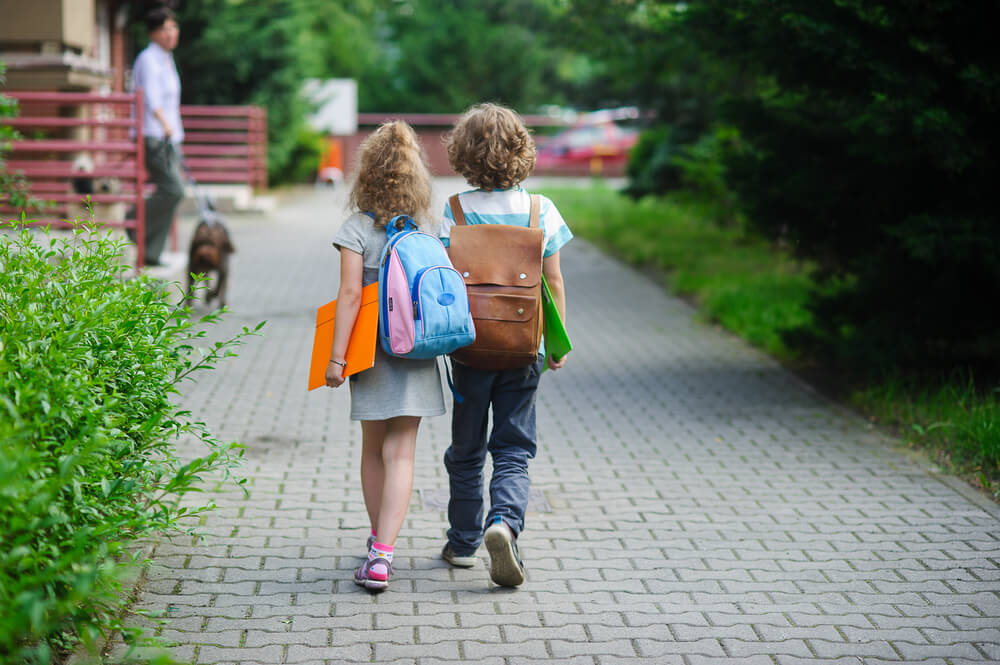 Boy and girl walking to school hand in hand with school bags behind the back