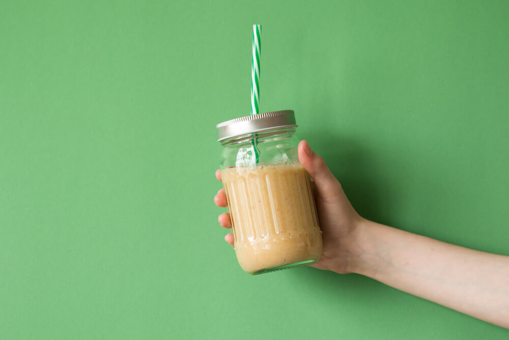 Woman's hand holding smoothie shake against colored wall