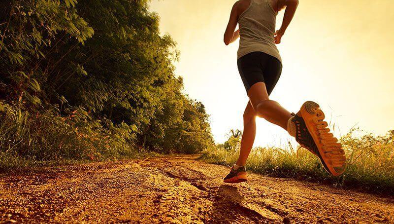 runner on dirt road at sunset