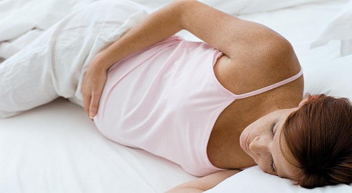 pregnant woman lying on bed holding stomach
