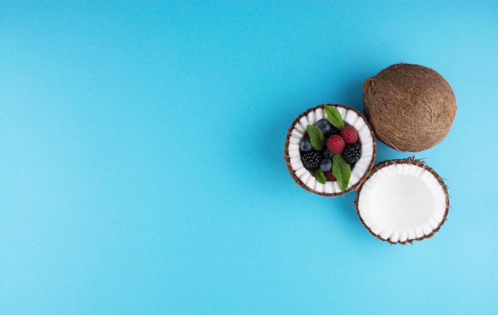Open coconuts on blue background with mix of berries