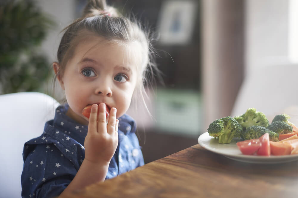 little girl snacking on vegetables at the table