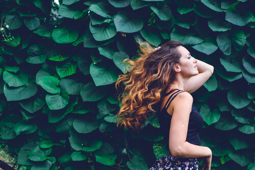 young woman with curly hair flowing against background of green leaves