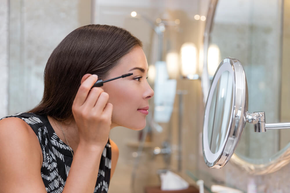 Woman getting ready for work doing morning makeup routine putting mascara in bathroom mirror at home