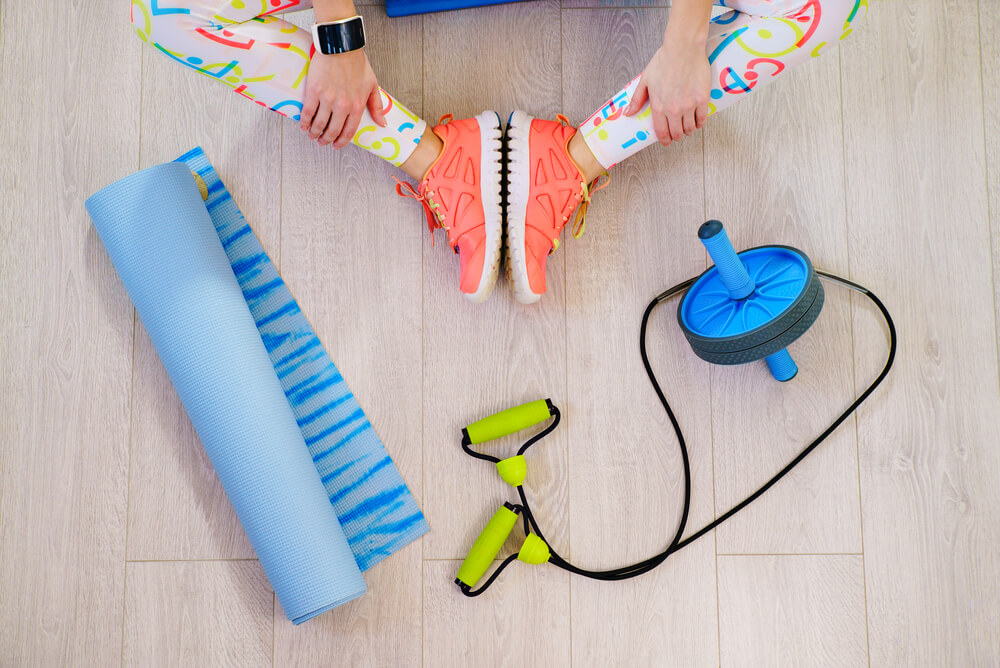 top view of woman's legs in butterfly next to fitness equipment