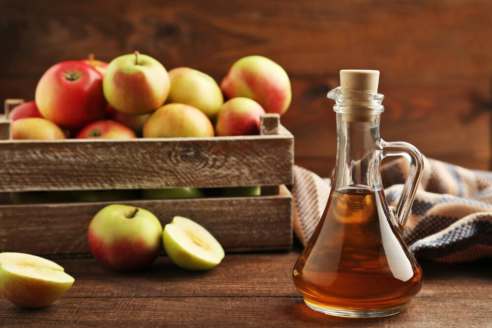 Apple cider vinegar in glass bottle on brown wooden table