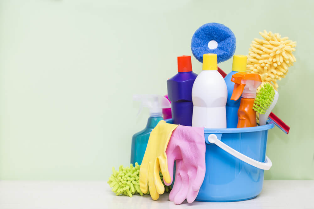 House cleaning product on wood table with green background