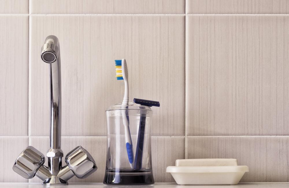 toothbrush & razor in glass next to water tap