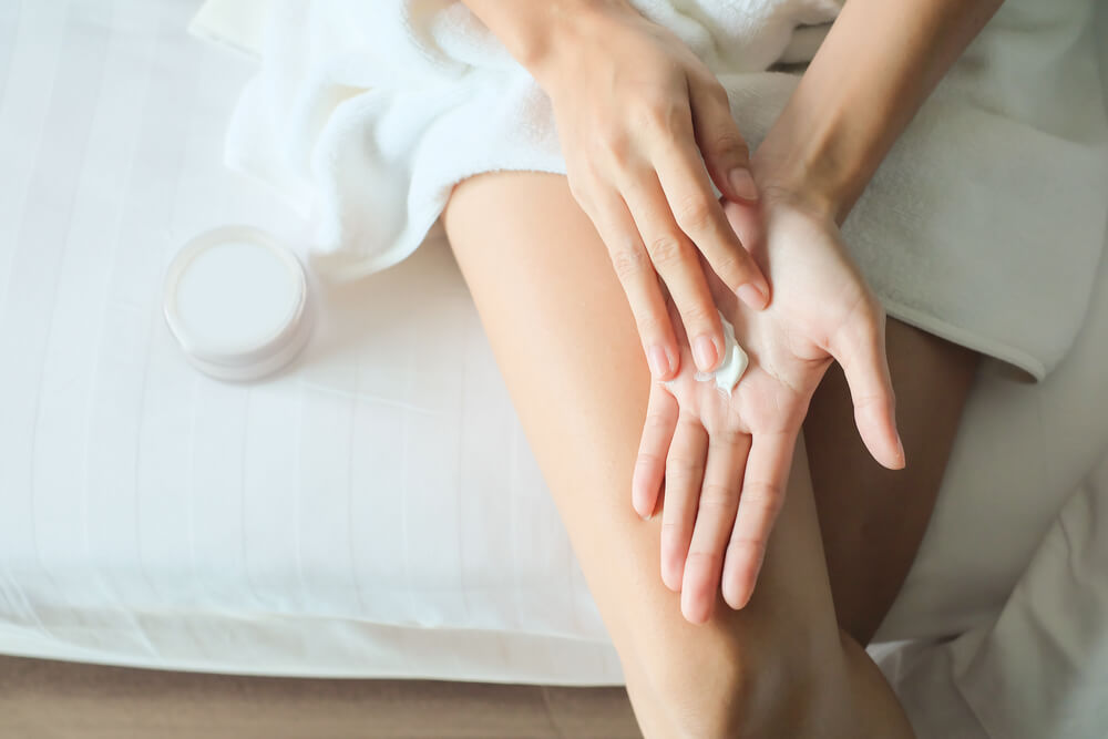 woman sitting on bed in towel and applying cream on hand