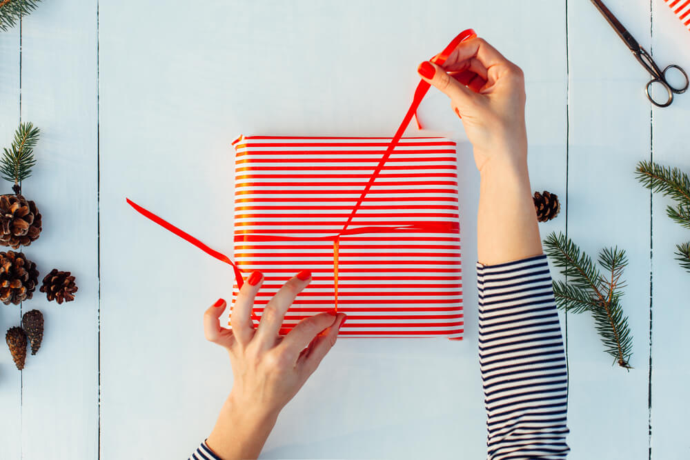 top view of woman wrapping gift box in red striped paper with red ribbon