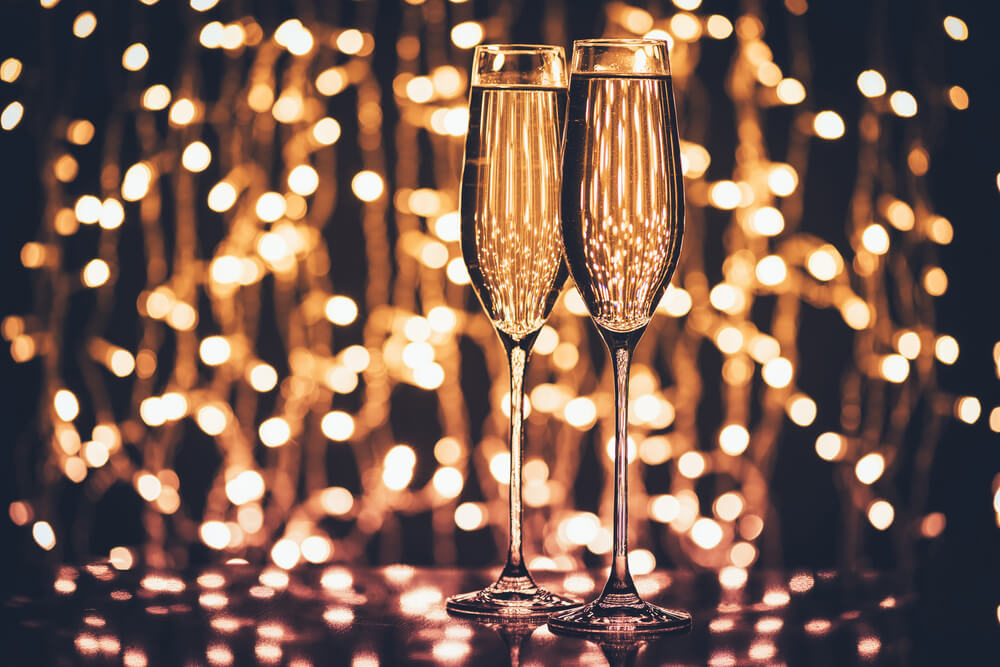 selective focus of 2 glasses of champagne against festive lights