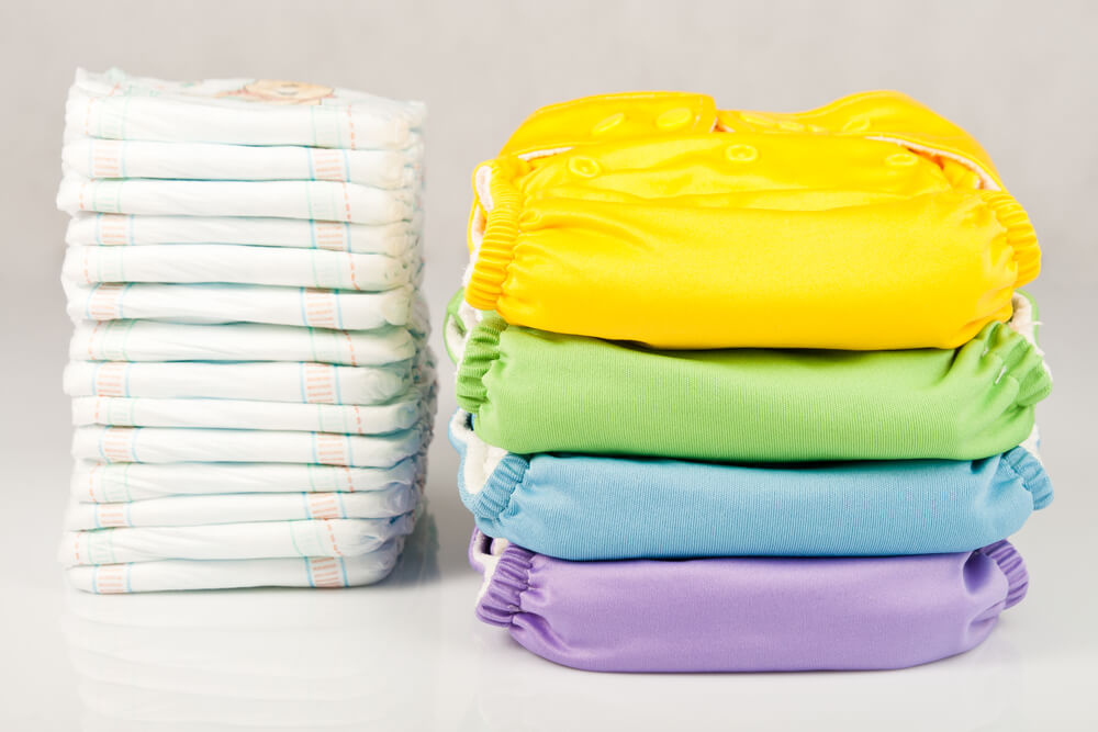 stack of disposable diapers next to stack of colourful cloth diapers