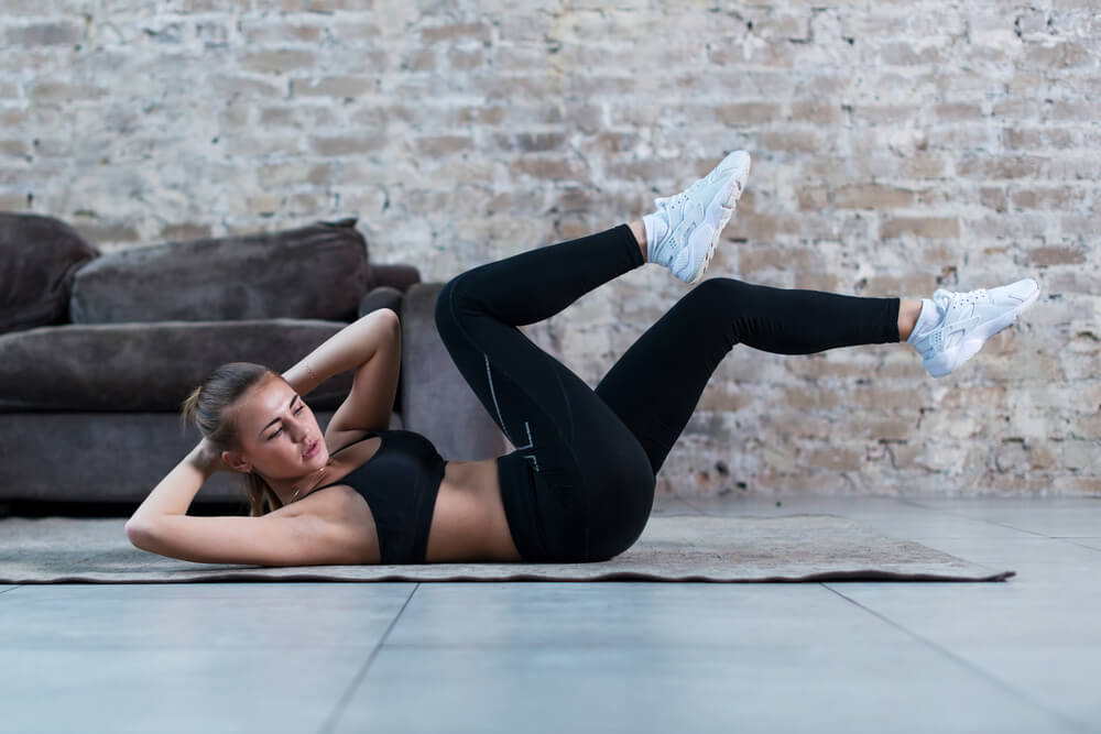 sporty young woman doing cross-leg crunch exercise on rug at home