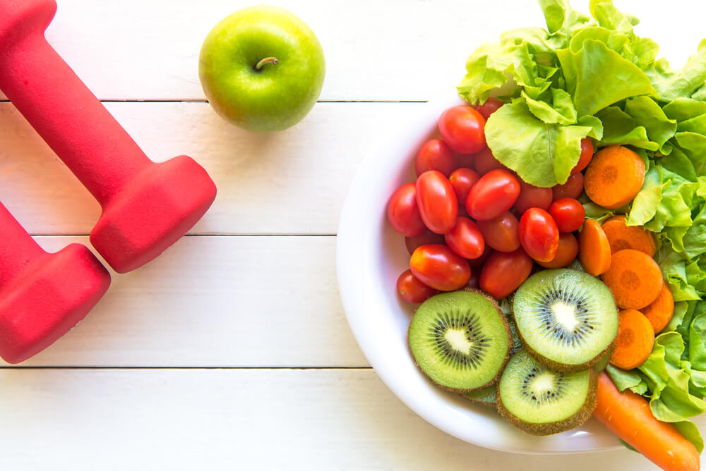 Top view of plate of vegetables, apple, and red hand weights on a white wooden table