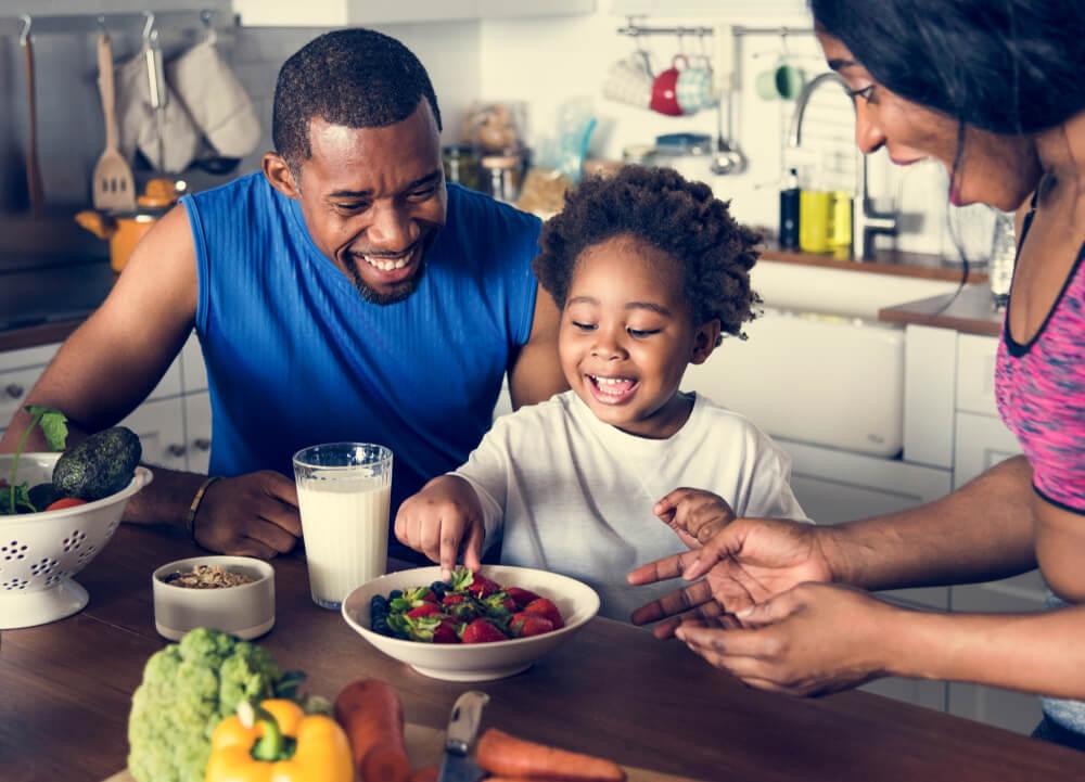 Parents smiling as child eats