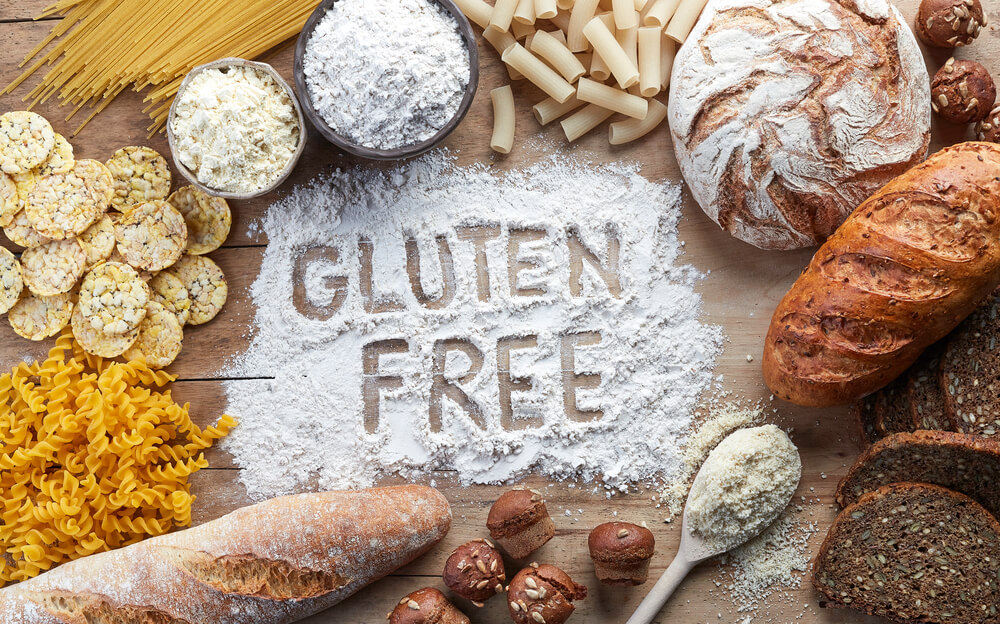 Gluten free food written in flour surrounded by pasta, bread, snacks and flour on wooden background from top view