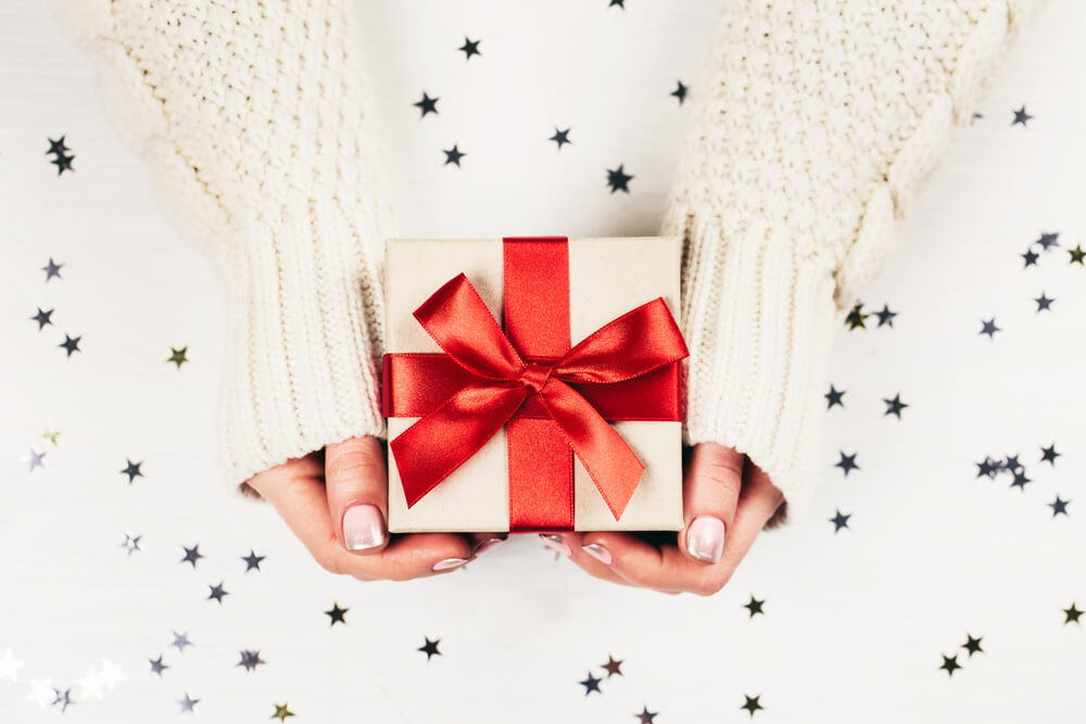 Female hands holding present with red bow on white rustic sparkling background
