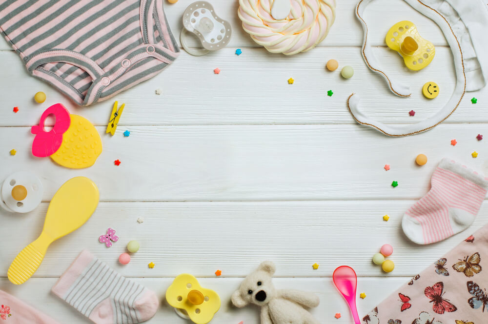 Baby accessories background: baby jumpsuit, socks, soother and toys over white wooden background with copy space