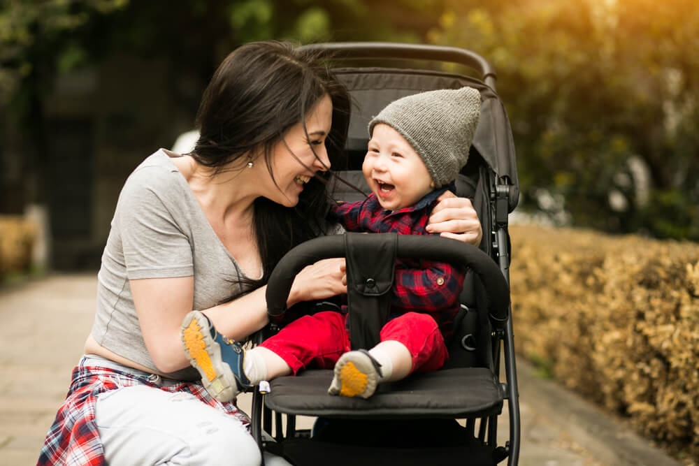 Mother Laughing with baby in stroller