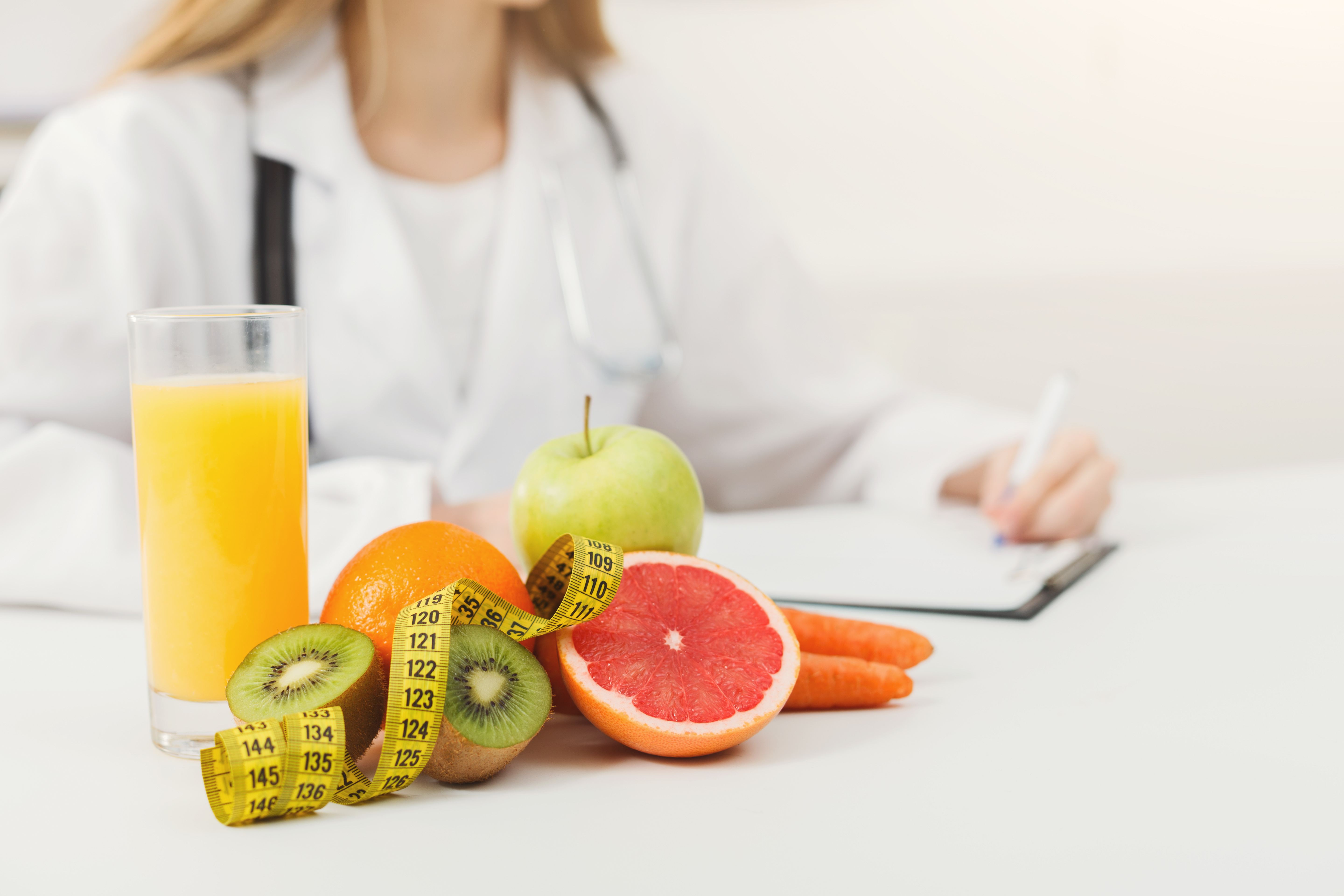 Nutritionist desk with healthy fruits, juice and measuring tape