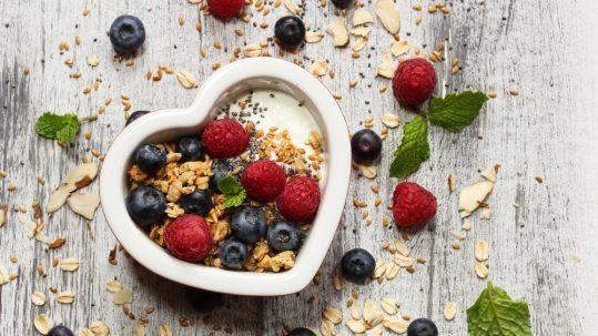 breakfast Muesli in heart shaped bowl with blueberries raspberries granola chia seeds