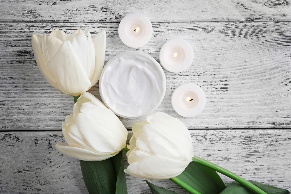 cosmetic cream with tulips on white wooden background