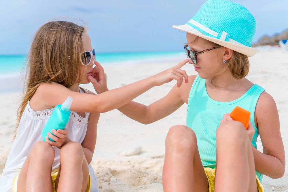 Sisters applying sunscreen to each other's noses on the beach