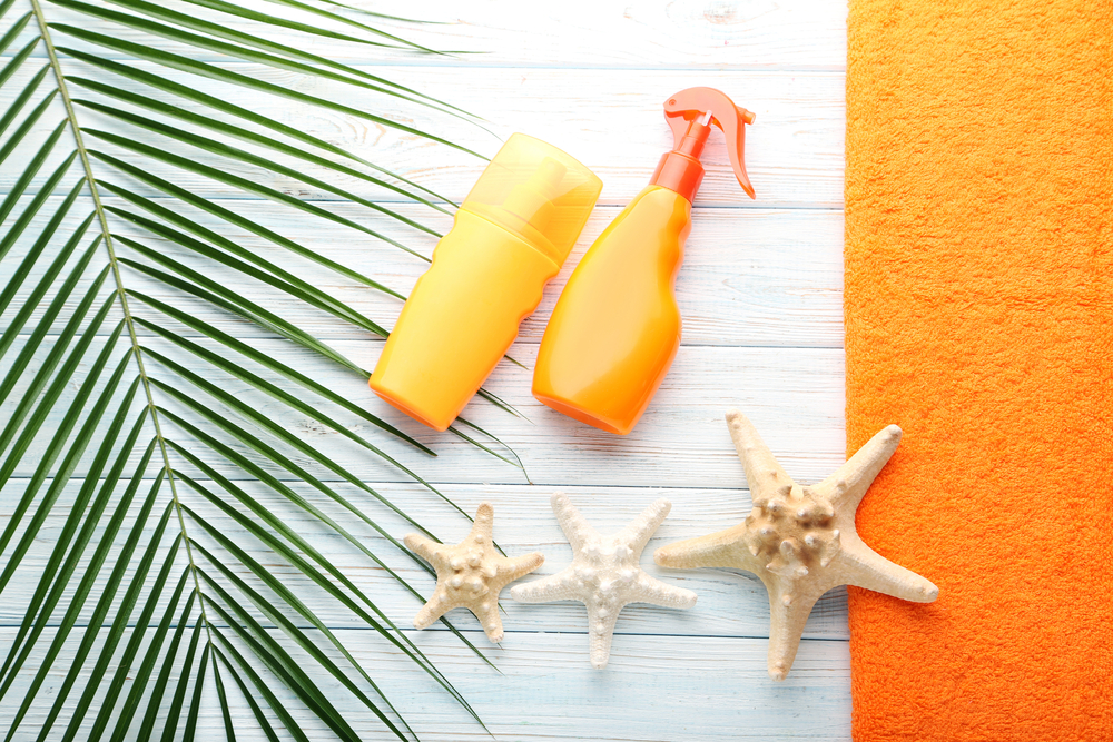 Sunscreen with starfish on wooden table