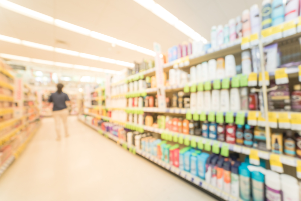 blurred image rows of hair care, skin care, cosmetic, sunscreen and lotion sprays products on display at pharmacy store