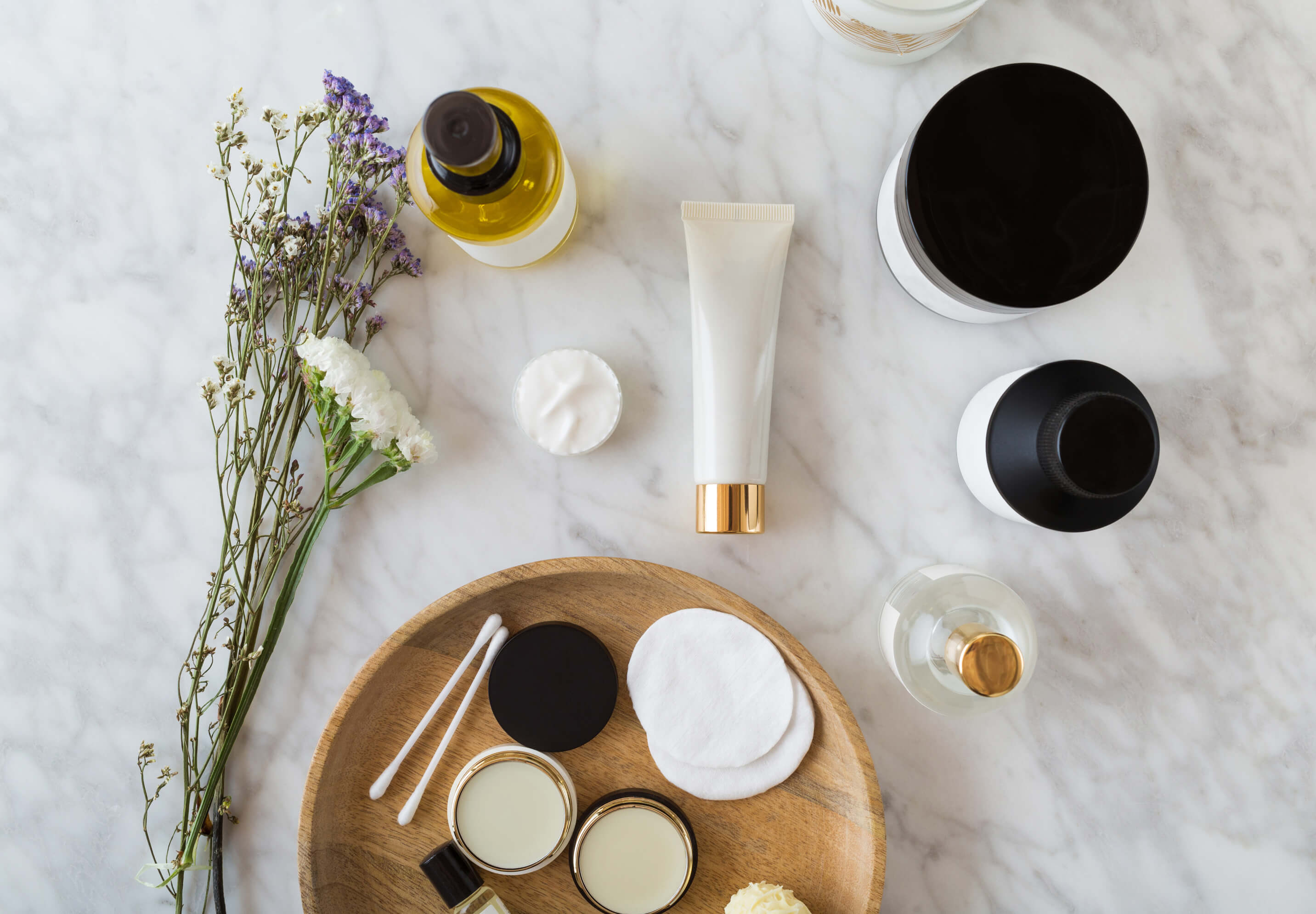 Beauty Product Flatlay on White Marble Table