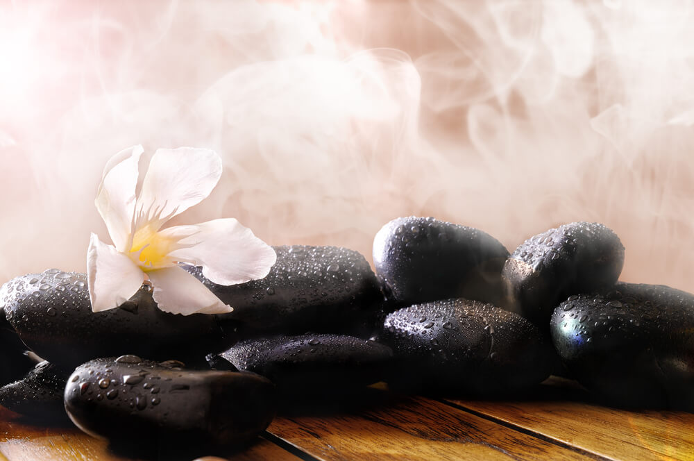 Group of black stones on wood base, steam background. Sauna, therapy, relaxation, and health concept