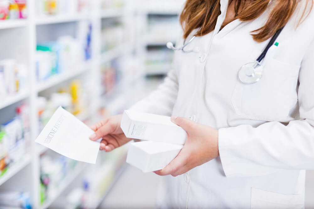 Pharmacist hands holding box container of medicines from shelf close up