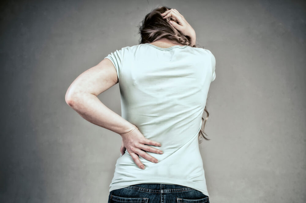 oman with back pain holding her aching back