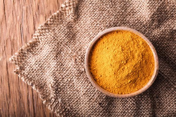 dry spice turmeric in a wooden bowl on a vintage background