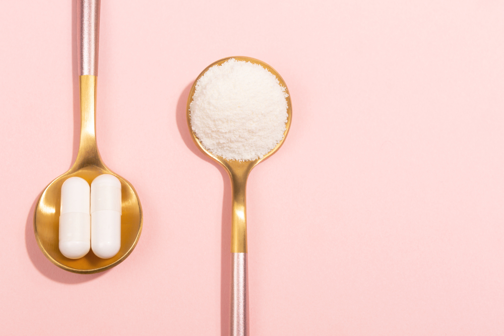 two gold spoons on a light pink background. In one spoon there's two white pills, in another it's white powder.