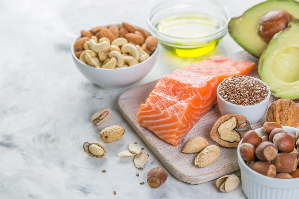 Food displayed on a charcuterie board and in small bowls including salmon, olive oil, nuts, and avocados