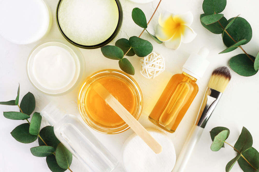 Flat lay of plant leaves, products, and makeup brushes