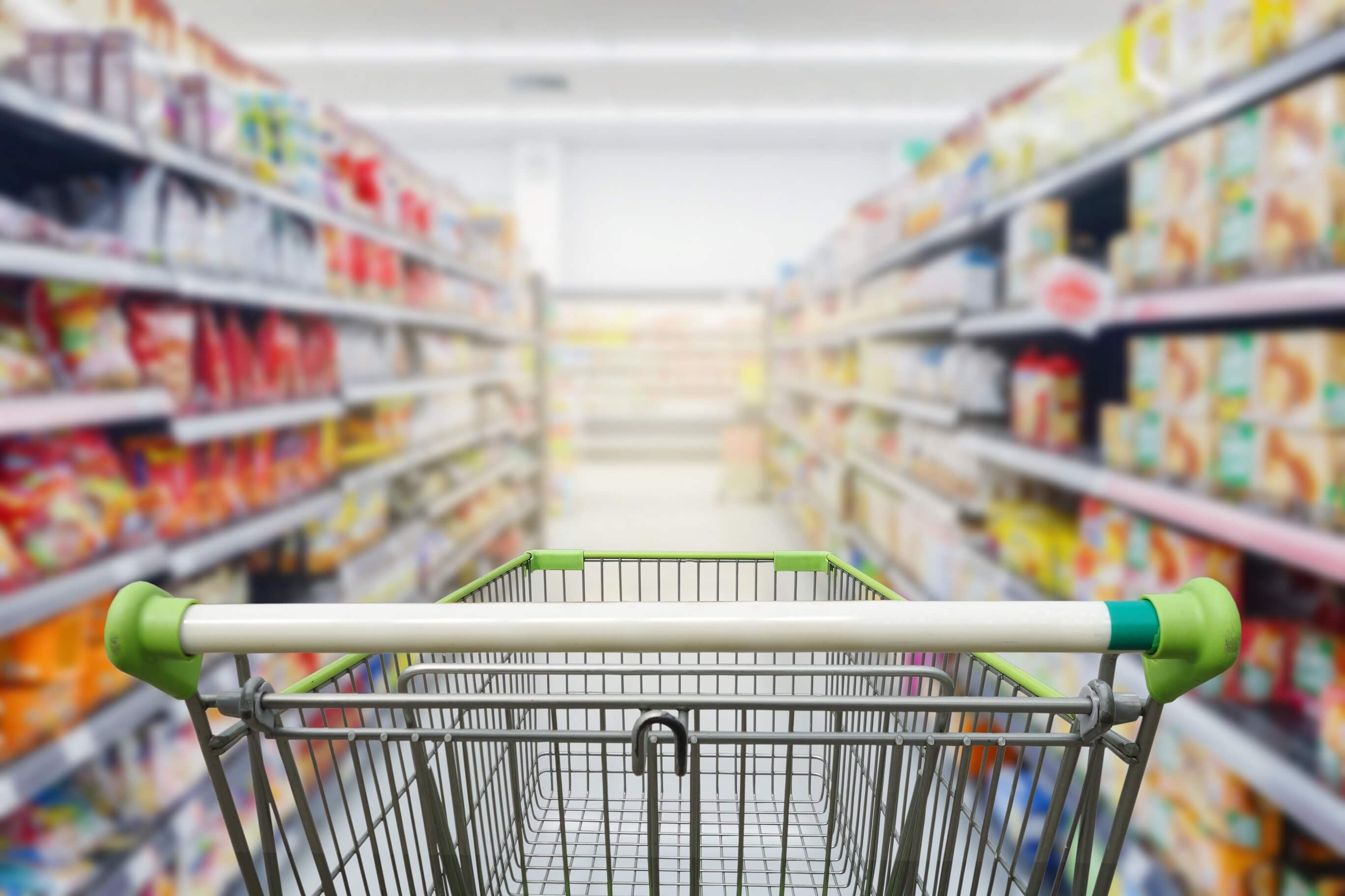 Empty grocery cart in an aisle of processed foods
