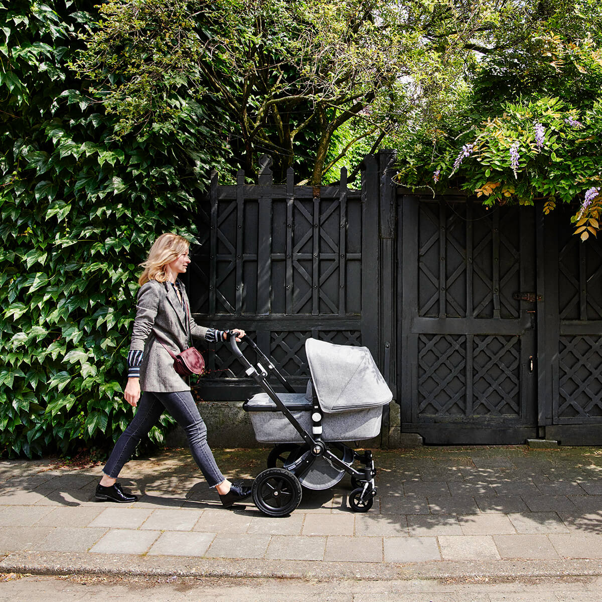 Woman pushing stroller on sidewalk on sunny day