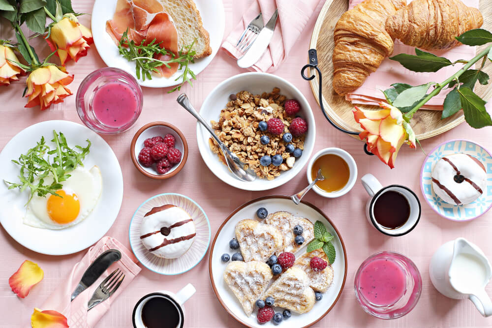 Flat lay of brunch items on a light pink background
