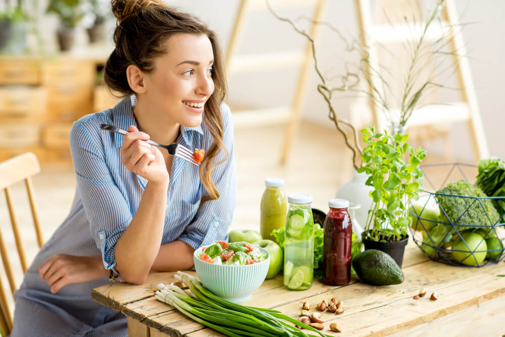 Woman in blue shirt eats salad surrounded by green vegetables and plants