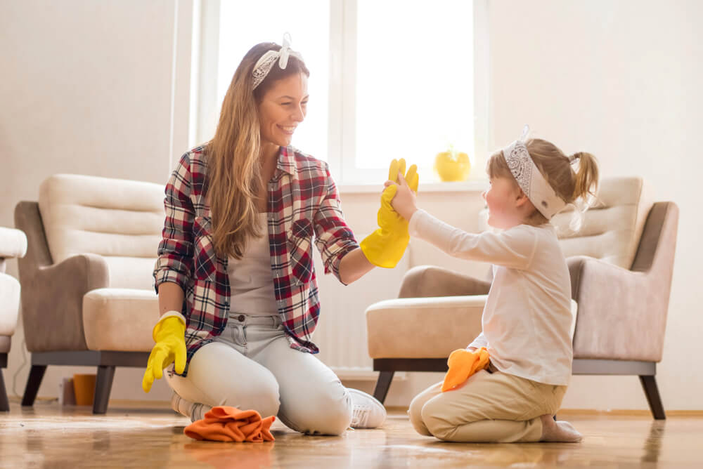 Mother and daughter high five while sitting on the floor in a living room surrounded by cleaning supplies