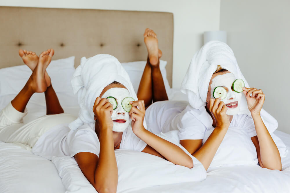 Two girls apply face masks and cucumbers