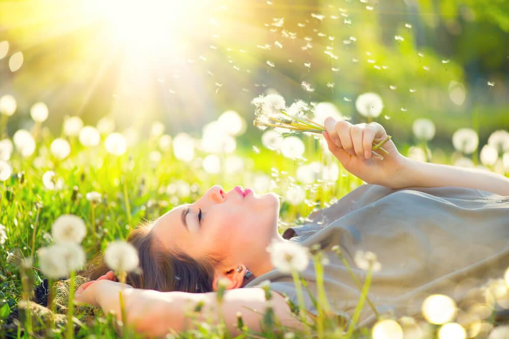 Woman lying in field of dandelions