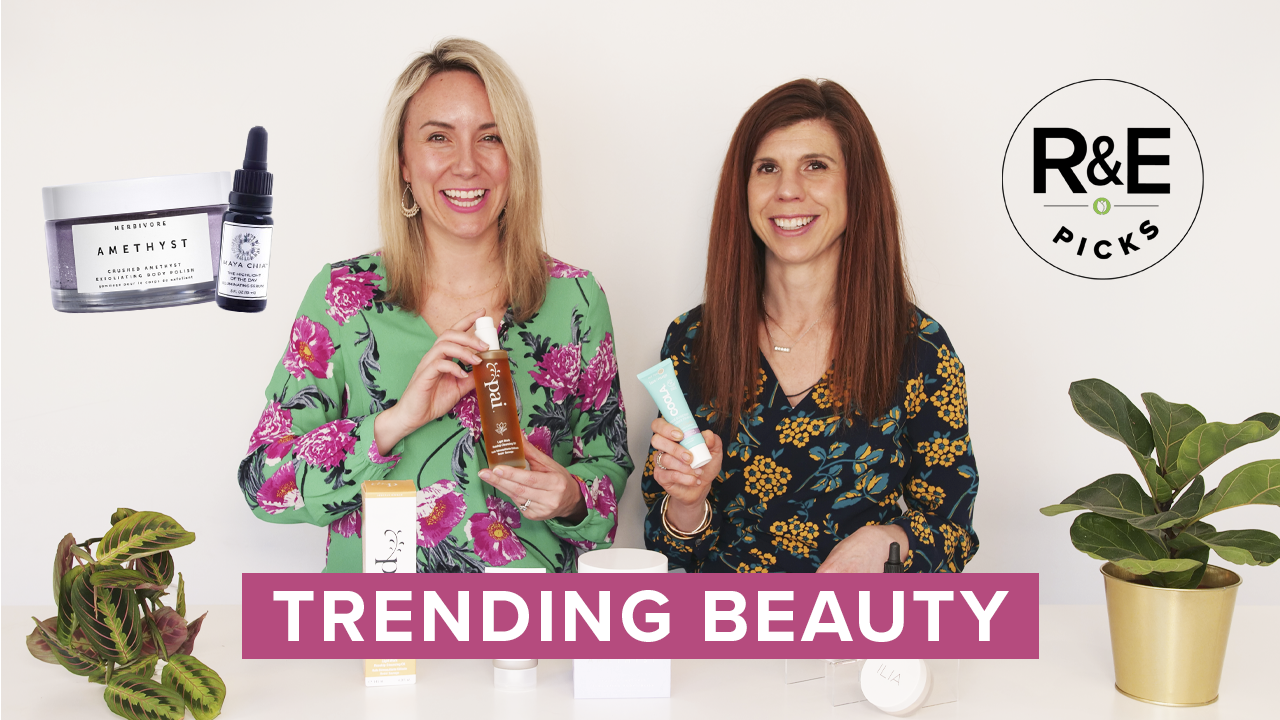 Two women hold beauty products surrounded by plants