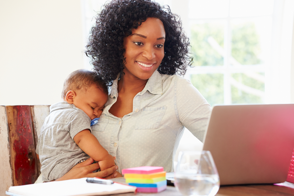 Mother working on laptop while baby sleeps