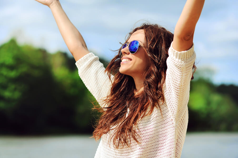 Woman smiling outside with hands in the air