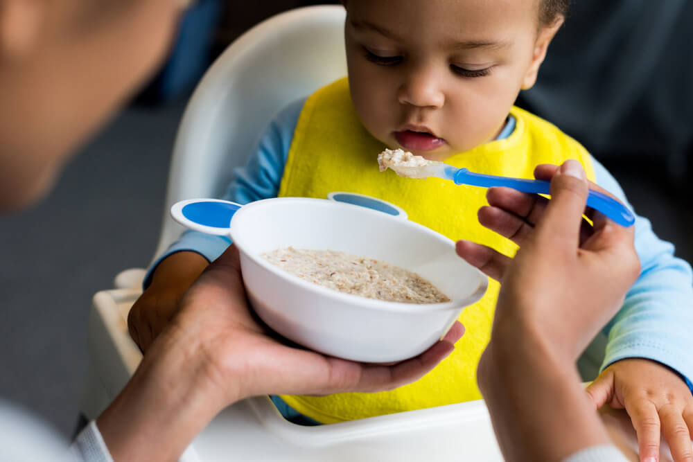 mom feeding baby oatmeal from bowl